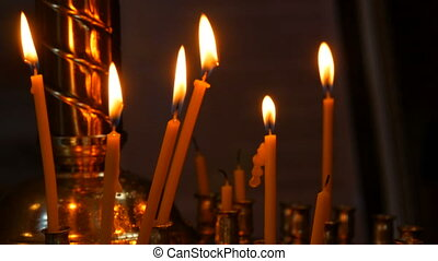Long thin wax candles burn with a flame in an Orthodox church, memorial rituals for Christians.