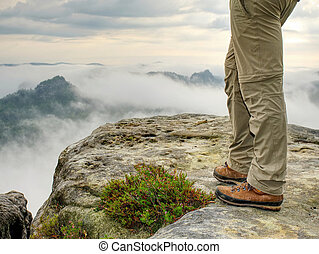 Long tired male legs in hiking trousers stay for moment on peak
