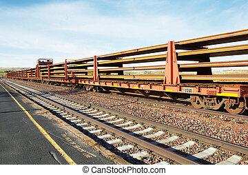 Long and empty train cars stretch to infinity agianst soft blue sky of North Dakota