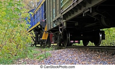 Long train running fast on railway on beautiful autumn...