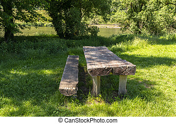 Long tree table with wooden benches in a meadow by the river.
