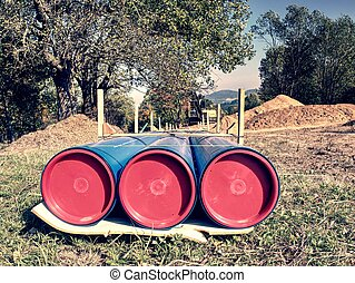 Long tube on ground. Colorful thick wall of plastic pipe