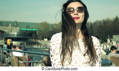 Long waving hair of the beautiful woman in white dress standing on the deck of a boat. Slow motion shot