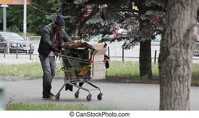 Long way - Vagabond pushing the cart full of trash on his...