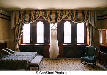 Long white dress of the bride on a hanger by the window in a room with an armchair and a bed.