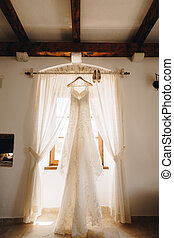 Long white dress of the bride on a hanger on the cornice with women's shoes at the window with open curtains in the room.