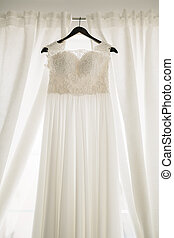 Long white dress of the bride with a lace corset on a black hanger against a background of white curtains.