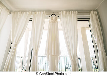 Long white dress of the bride with a lace corset on a black hanger on the ceiling on the cornice against the background of white curtains in the room.