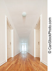 Long white interior passage with parquet floor - View down a...