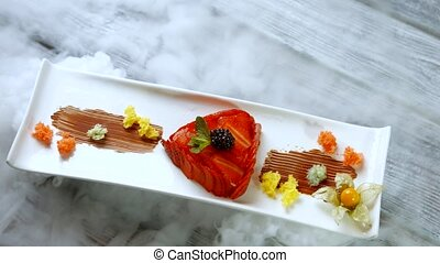 Long white plate with dessert. Slices of red strawberry....