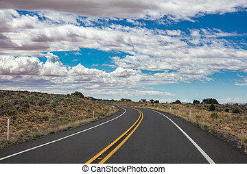 Long winding highway in the american countryside, blue sky with clouds