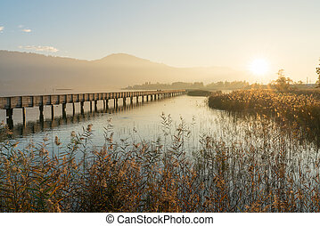 long wooden boardwalk pier over water in golden evening light with a mountain landscape silhouette in the background and golden marsh grass in the foreground