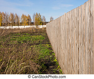 Long wooden fence on the field