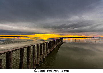 long wooden jetty on a frozen lake during sunset with rain clouds in the winter