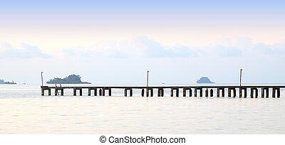 Long wooden pier port on morning beach.
