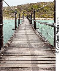 Long Wooden Suspension bridge over a lagoon