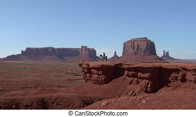 long zoom in on cowboy and horse in Monument Valley Utah