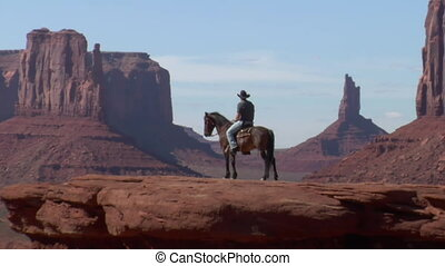 long zoom shot of cowboy, horse, and Monument Valley