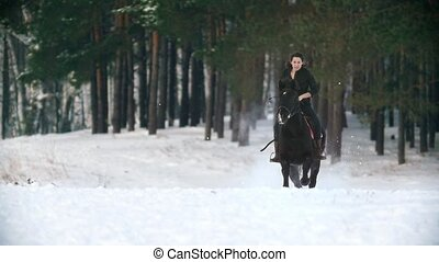 Longhaired woman riding a black horse through the deep...