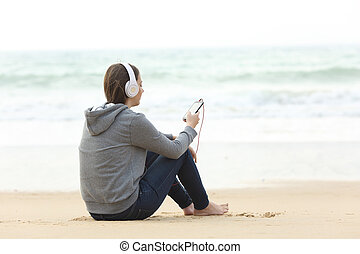 Longing teen alone listening to music on the beach