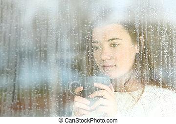 Longing teen looking through a window alone