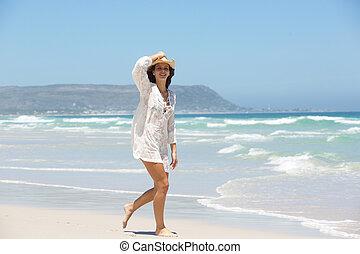 longitud completa, de, un, mujer joven, el caminar en la playa, con, sombrero