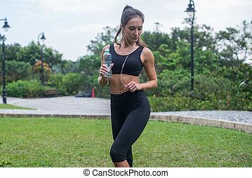 longitud completa, tiro, de, hermoso, condición física, hembra, modelo, en, negro, ropa de deporte, posición, en, pasto o césped, en, parque de la ciudad, y, escuchar música, en, audífonos, tenencia, un, botella