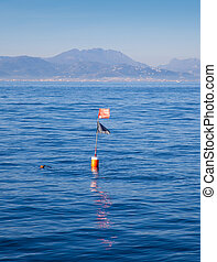 Longliner and trammel net buoy with flag pole in blue sea