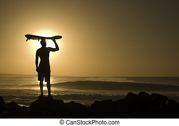 A longboarder watching he waves at sunset in La Santa Lanzarote