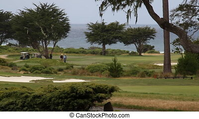 longshot of golfers and ocean in distance