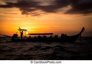 Longtail boat in sea at sunset in Thailand