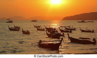 Longtail boats on seashore at sunset
