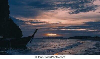 Longtail boats parked near beautiful Phra Nang Beach during sunset.