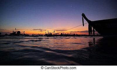 Longtail boats on seashore at sunset