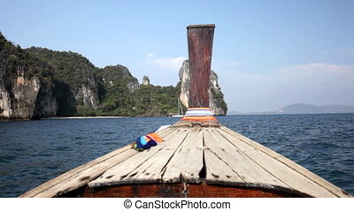 Longtail floats by rocks in the Andaman Sea