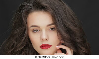Look a young attractive woman. Portrait of beautiful woman on black background. Beauty Model with Perfect Fresh Skin. Caucasian female model isolated on black background. Perfect fresh skin. Pure beauty model female looking at camera. Beautiful girl touching her face. Caucasian female model isolated...