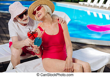 Mature woman wearing red swimming suit looking at her husband