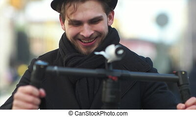 Caucasian adult man recording shots with electronic stabilizer while smiling at camera