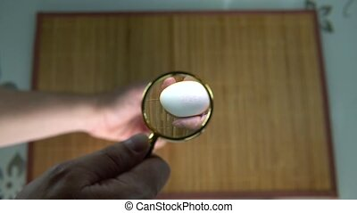 Look at the egg under the magnifying glass blurred background view from above, the brown background on the table increase in size