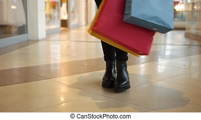 Look at the legs of a woman walking with shopping bags around the mall