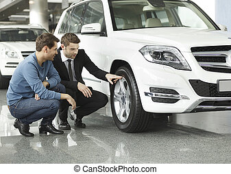 Look at these tires! Young car salesman showing the ...