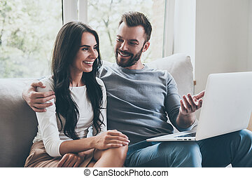 Look at this! Beautiful young loving couple looking at laptop and smiling while sitting together on the couch