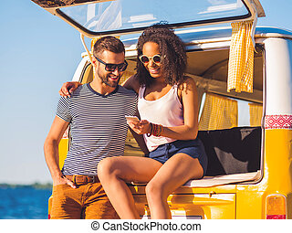 Look at this photo! Cheerful young couple looking at mobile phone together while both sitting at the trunk of retro minivan with sea in the background