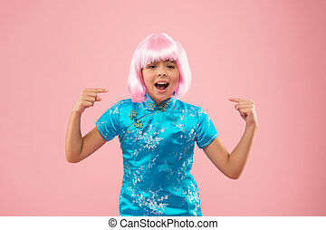Look at this. Unhappy girl pointing fingers at wig. Small child pointing pink background. Fashion and beauty. Pointing gesture. Nonverbal communication. Pointing for attention. Hair salon