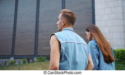 Look from behind at man and woman in jeans jackets walking on the street