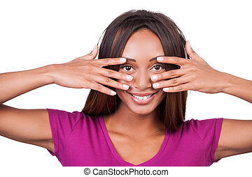 Look in my eyes! Attractive young African woman holding fingers on her face and smiling while standing isolated on white