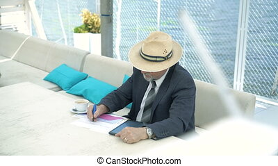 Look of old man working with tablet and diagrams in cafe....
