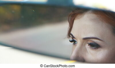 look of the driver`s wife in the rearview mirror -...