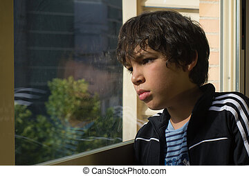 a sad boy looking out through a window