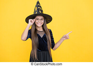 look over there. cheerful kid create miracles. carnival costume party. trick or treat. celebrate the holidays. wizardry. halloween witch girl. happy childhood. teenage child in witch hat and glasses